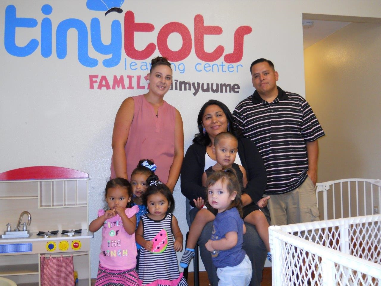 family standing in front of a sign